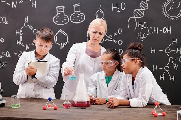Grupo de alunos espertos do ensino médio de jaleco e óculos, fazendo anotações e olhando para o professor mostrando experimento químico