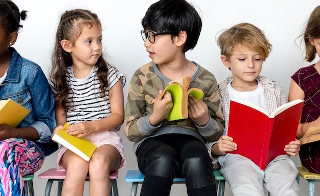 Grupo de alunos está sentado e lendo um livro.