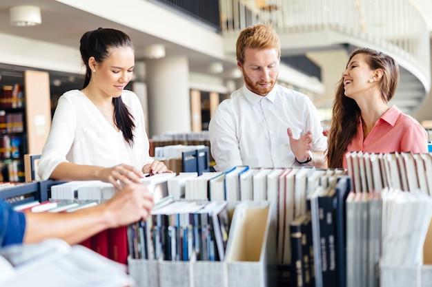 Grupo de alunos estudando na biblioteca e lendo livros