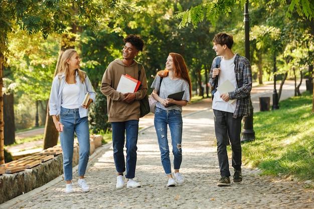 Grupo de alunos felizes caminhando pelo campus