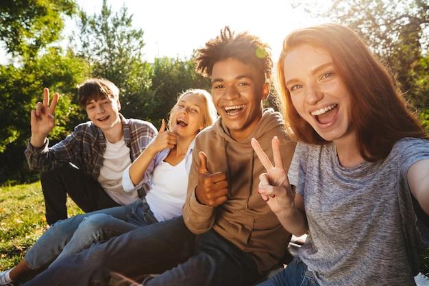 Grupo de alunos multiétnicos felizes fazendo lição de casa
