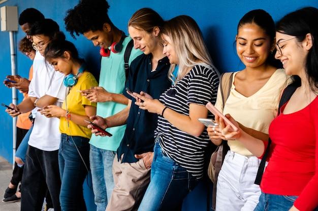 Grupo de alunos multirraciais do ensino médio usando celular. redes sociais educação