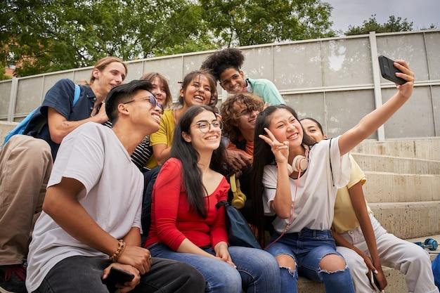 Grupo de alunos multirraciais tirando selfies com uma garota chinesa de celular mostrando os dedos