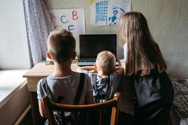 Grupo de alunos ou amigos usando fones de ouvido, sentados perto do laptop em casa, um aluno da escola familiar
