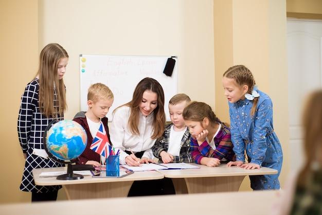 Grupo de alunos primários e professor trabalhando em mesas na sala de aula.