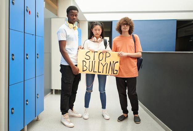 Grupo de alunos racialmente diverso se manifesta contra o bullying de alunos mais velhos da escola olhando para o ...