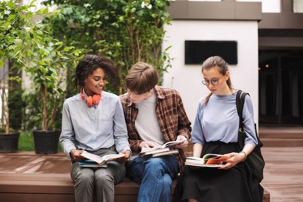Grupo de alunos sentados no banco lendo livros no pátio da universidade