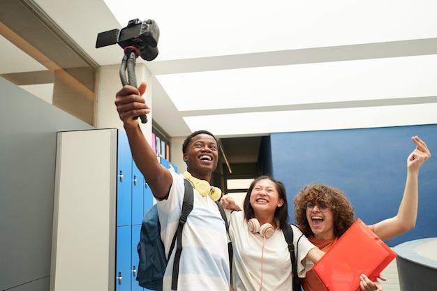 Grupo de alunos sorridentes, blogando na escola grupo multiétnico de jovens gravando um vídeo com ...