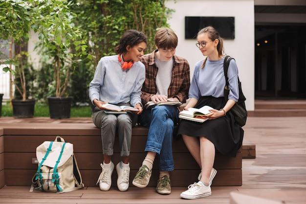 Grupo de alunos sorridentes, sentados no banco e lendo livros no pátio da universidade
