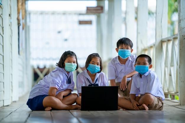 Grupo de alunos usando máscara protetora para protect against covid-19 usa laptop para ter aulas on-line alegremente em uma escola na tailândia.