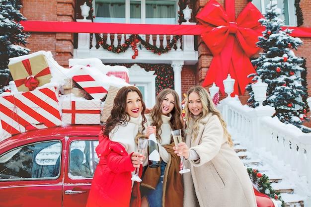 Grupo de amigas de meninas com champanhe no carro vermelho da casa no natal