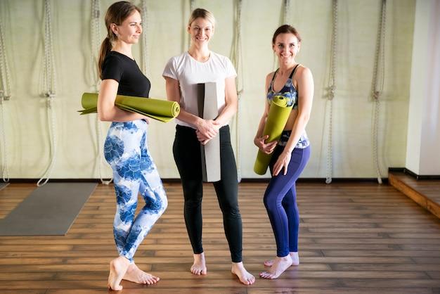 Grupo de amigas no sportswear sorrindo juntos em pé em uma academia após treino de ioga.
