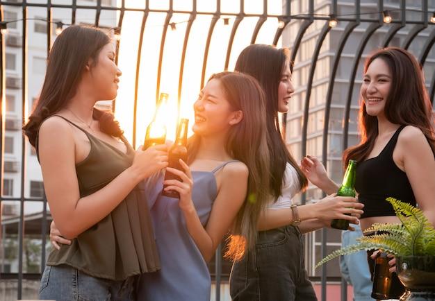Grupo de amigo asiático torcendo e bebendo na festa no terraço. jovens brindando copo com cerveja no restaurante do último piso