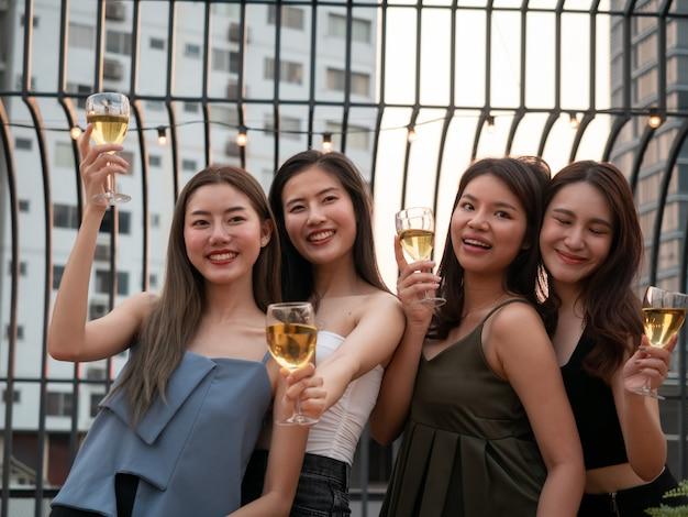Grupo de amigo asiático torcendo e bebendo na festa no terraço. jovens brindando copo com vinho no restaurante do último piso