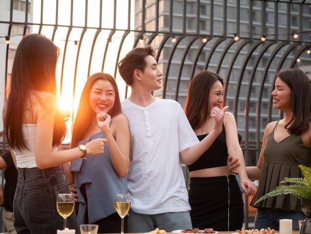 Grupo de amigo asiático torcendo e bebendo na festa no terraço. jovens curtindo e saindo no telhado ao pôr do sol