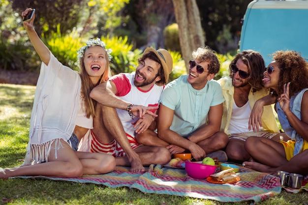 Grupo de amigo feliz tomando uma selfie no parque