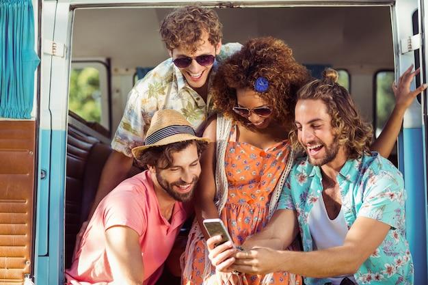 Grupo de amigo feliz usando telefone celular na caravana