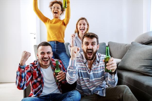 Grupo de amigo sentado na sala e torcendo por seu time de futebol favorito. todos eles segurando garrafas de cerveja.