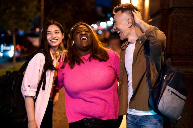 Grupo de amigos à noite nas luzes da cidade