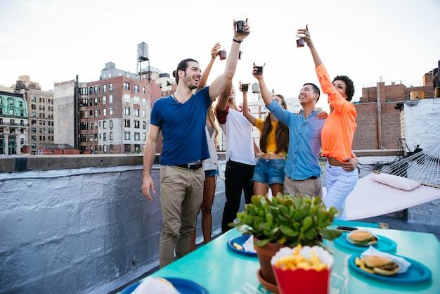 Grupo de amigos a passar tempo juntos em um telhado na cidade de nova york, conceito de estilo de vida com pessoas felizes