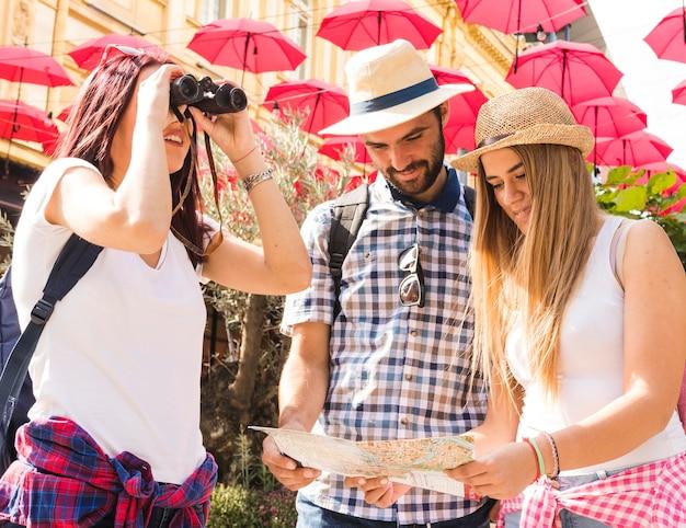 Grupo de amigos à procura de localização através de binóculos e mapa