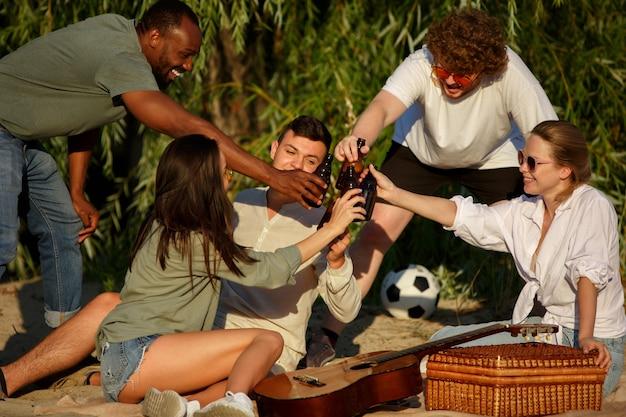 Grupo de amigos a tilintar em copos de cerveja durante um piquenique na praia