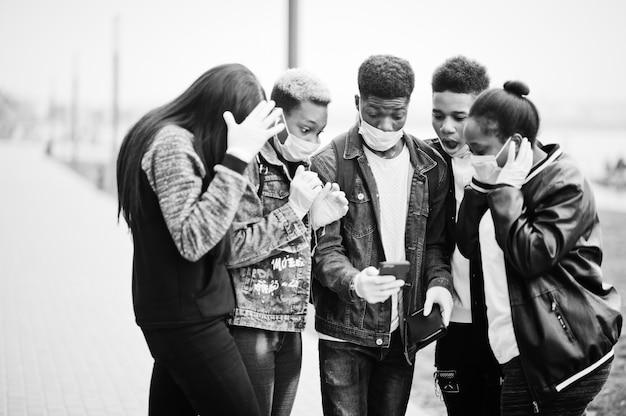 Grupo de amigos adolescentes africanos no parque usando máscaras médicas protege contra infecções e doenças quarentena do vírus coronavírus, leu notícias chocadas no telefone.