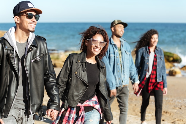 Grupo de amigos africanos felizes andando ao ar livre na praia.
