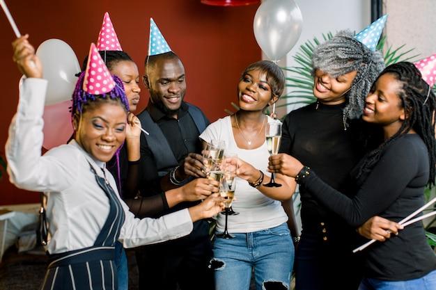 Grupo de amigos africanos felizes bebendo champanhe e comemorando a festa de aniversário