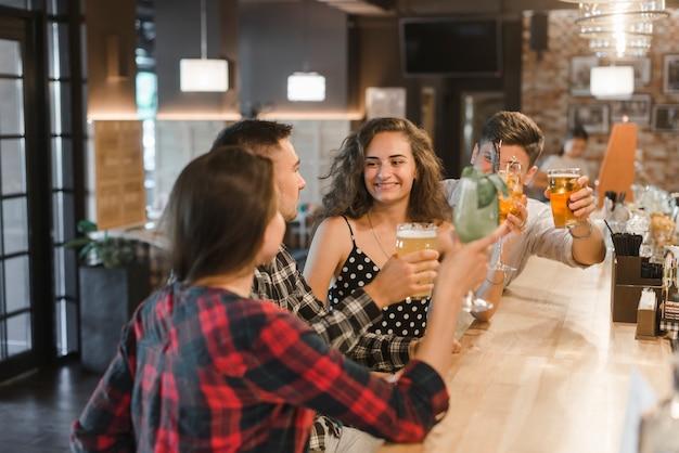 Grupo de amigos alegres, desfrutando de bebidas no pub
