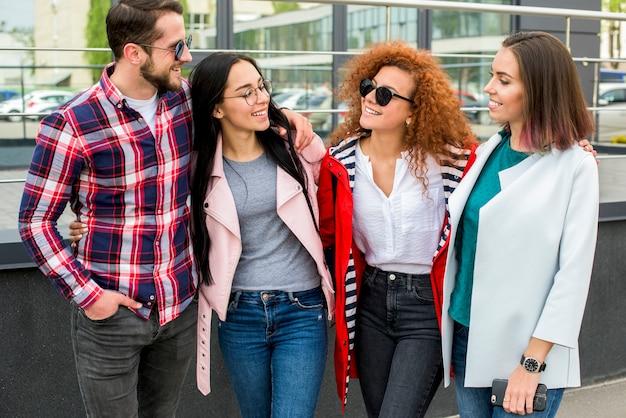 Grupo de amigos alegres em pé perto do edifício de vidro