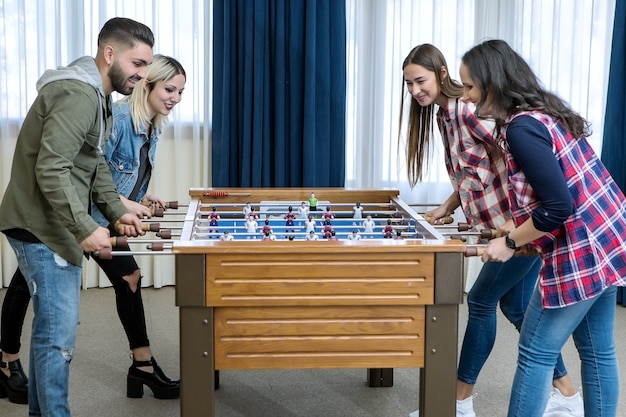 Grupo de amigos alegres jogando futebol de mesa