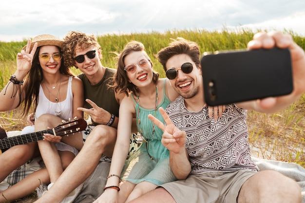 Grupo de amigos alegres passando um tempo juntos ao ar livre, bebendo cerveja, tocando violão