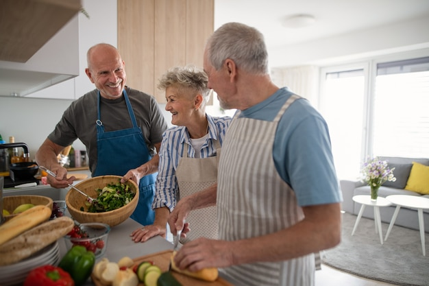 Grupo de amigos alegres sênior, festa dentro de casa, cozinhando e conversando.