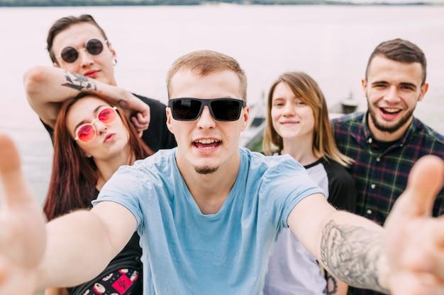 Grupo de amigos alegres tomando selfie