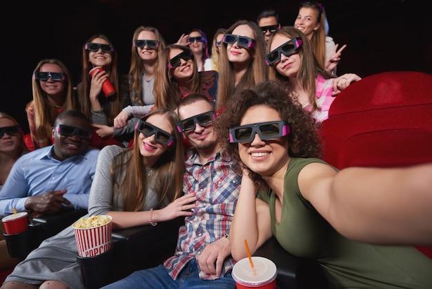 Grupo de amigos alegres usando óculos 3d sorrindo alegremente tirando uma selfie e relaxando no cinema juntos