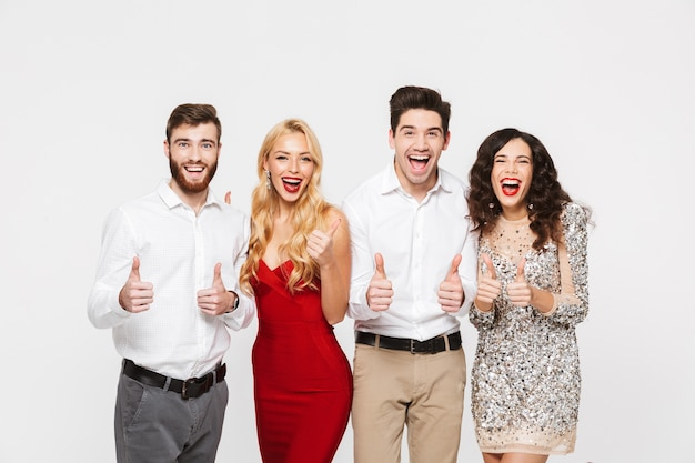 Grupo de amigos alegres vestidos de forma inteligente, isolados sobre o branco, comemorando o ano novo, mostrando os polegares para cima