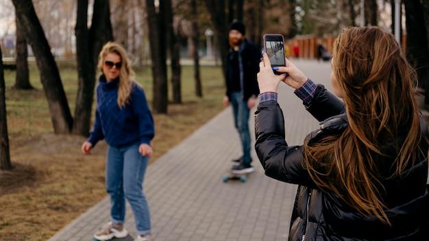Grupo de amigos andando de skate no parque enquanto uma mulher tira fotos