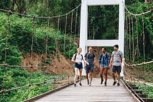 Grupo de amigos andando na ponte em uma aventura de paisagem tropical e conceito de viagem