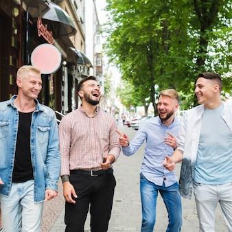 Grupo de amigos andando na rua tirando sarro