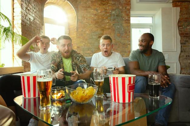 Grupo de amigos animados, jogando videogame em casa. jogadores ou fãs do sexo masculino que passam tempo e se divertem juntos em casa