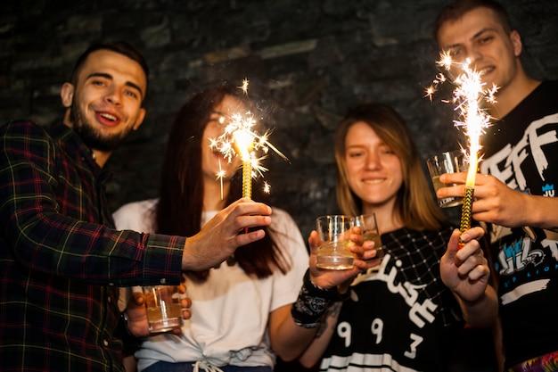 Grupo de amigos, apreciando as bebidas com brilho