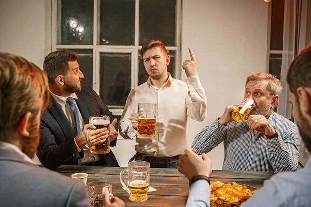 Grupo de amigos apreciando bebidas à noite com cerveja na mesa de madeira