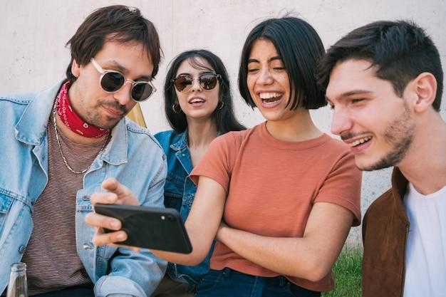 Grupo de amigos assistindo algo no smartphone.