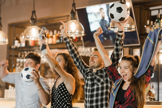 Grupo de amigos assistindo esporte juntos comemorando a vitória no bar