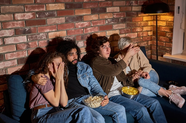 Grupo de amigos assistindo filme de terror na tv em casa, comendo pipoca, sentados no sofá juntos, fechando os olhos, dois casais nervosos assustados em estado de choque apavorados