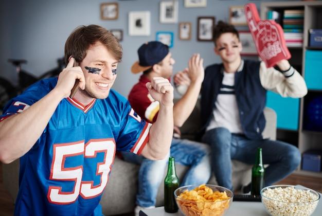 Grupo de amigos assistindo futebol em casa