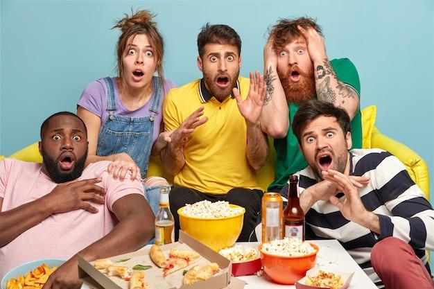 Grupo de amigos assustados assistindo filme de terror