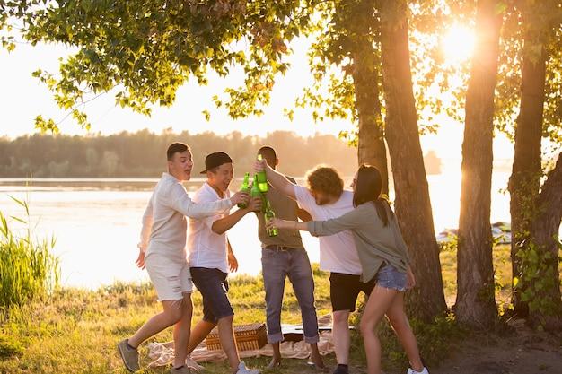 Grupo de amigos batendo garrafas de cerveja durante um piquenique na praia, estilo de vida, amizade se divertindo