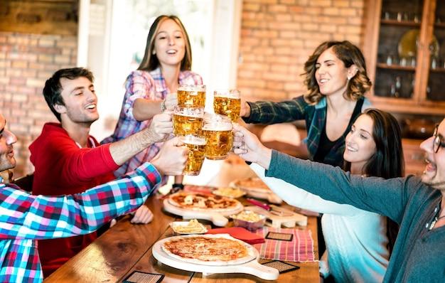 Grupo de amigos bebendo cerveja e comendo pizza em bar restaurante - conceito de amizade com jovens se divertindo juntos na pizzaria risto pub no happy hour - foco em copos de cerveja - filtro quente